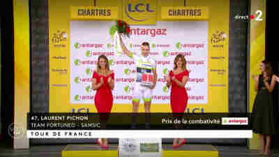 [image: a cyclist (male) with two girls around him on the victory podium and a third girl not too far]